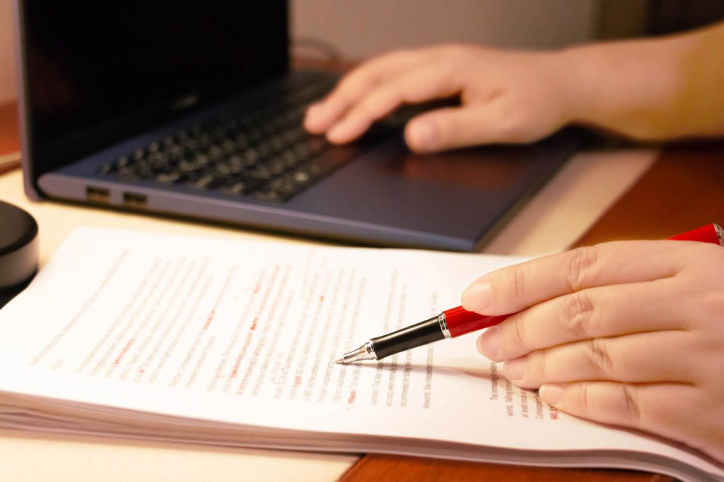 Hands on a computer and paper with a red pen in the left hand