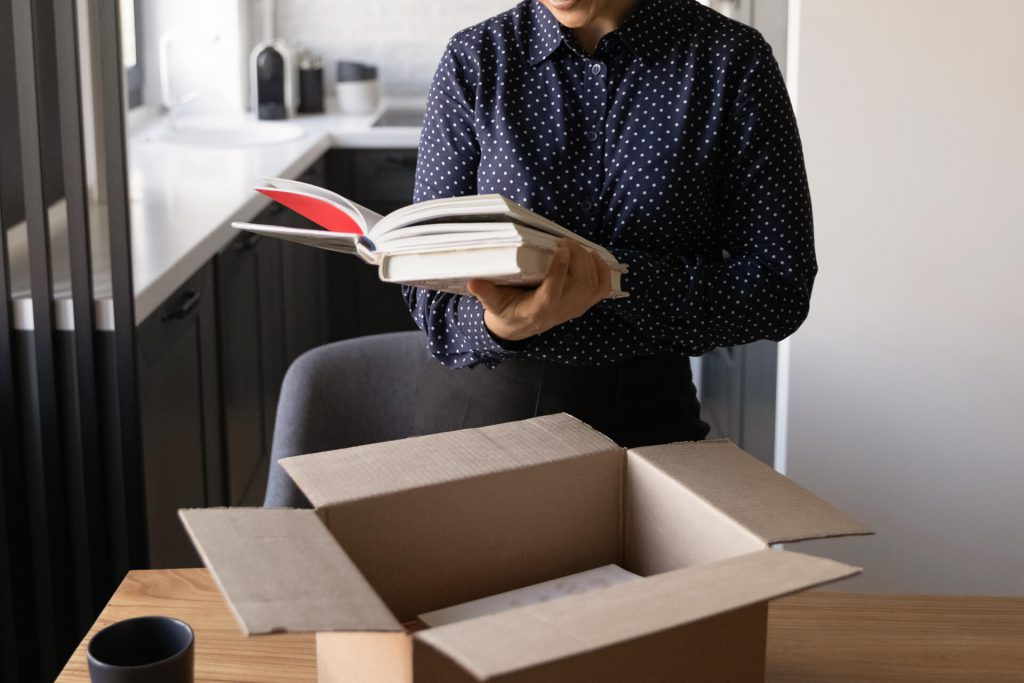 Women in blue shirt opening a box with a book in hand.